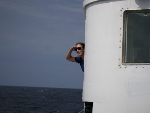 NOAA Corps Officer ENS Rachel Pryor steering the Oregon II during a morning haul back.