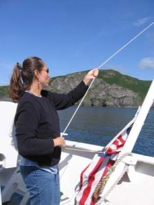 TAS Kim Wolke raising the American flag on the fantail of NOAA ship RAINIER