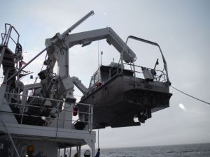 One of the launches is lowered from the ship.