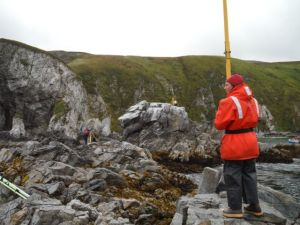 I am holding the survey rod on top of a benchmark.