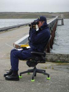 NOAA Corps ENS Clark demonstrates proper form for tide gauge observation.