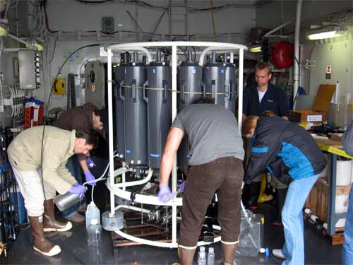 The scientists all getting their water samples out of the 30 liter bottles.