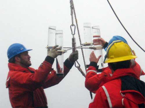 The scientists are carefully retrieving the tubes of brine that for the past 24 hours have collected ocean sediments.