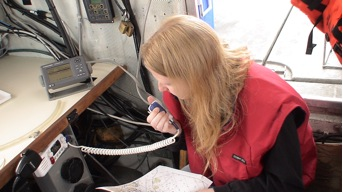 Amy, a survey technician operates the radio on the launch to maintain communication with the RANIER while operating miles from the ship.