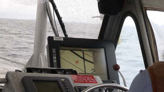 This photo was taken looking over the shoulder of the coxswain who is in charge of the boat and steers the boat to keep it on the desired course. The orange airplane icon shows the direction of the boat and keeps the launch on the survey lines designated by the survey tech in the forward cabin.