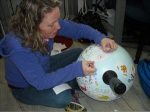 Me decorating the Drifter Buoys with the student's stickers on the lab floor.