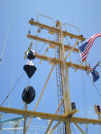 Day shapes displayed on the Nancy Foster ship mast;  black ball, diamond, and black ball.  The NF has restricted ability to move; the ROV is in the water.