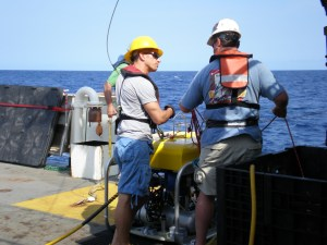John receiving launch instructions from Andy David; including about how the cable attaches to the ROV and the fiber optic line.