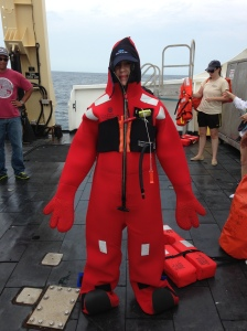 I'm dressed in a survival suit looking a bit like an orange Gumby.  These survival suits would protect us from hypothermia if we needed to abandon ship. In order to wear these, you must lay the suit flat on the floor and crawl into it. It took Ensign Laura Dwyer, a Junior Officer, and me working together to get it on. I really was tempted to Sumo wrestle with it on!