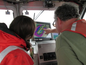 Hydrographer in Charge (HIC) Starla Robinson and Seaman Surveyor Dennis Brooks look over multibeam data together, as they safely plan next steps to survey in shoal, rocky waters.