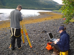 Assistant Survey Tech Eli Smith sets up for a level run while ENS Micki Ream prepares for data collection.