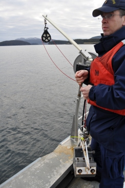 ENS Steve Wall collecting a bottom sample.