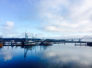Commercial fishing boats are docked for the night, with the Yaquina Bay Bridge in the distance.