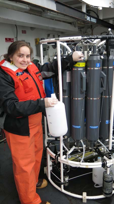DJ Kast helping Jessica collect her 4 L of seawater from the Niskin bottle in the Rosette. Photo by Jerry P.