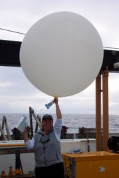 TAS Jane Temoshok holds up a weather balloon and its attached radiosonde.
