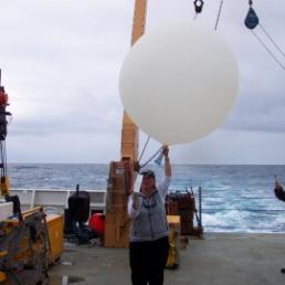 TAS Jane Temoshok readies a weather balloon for launch.