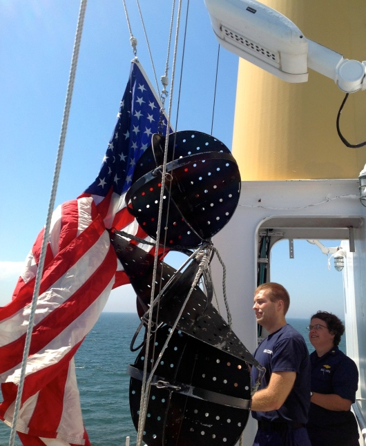 Lieutenant Commander Hauser and Ensign Anderson with the American Flag.