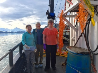 Cheryl, Kathy, and Mary stand with a large sample of red tree coral hung out to dry