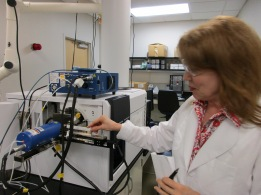 Cheryl uses this machine to look closely at how molecules act. Based upon how the microscopic parts fall down the white tube behind her, after they are thrown up, she can find out if illegal drugs were used to make a fish live longer!
