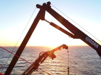 Mechanical cranes on NOAA ship Bigelow with sun rising in background