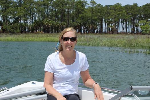 Susan on a boat in salt marsh