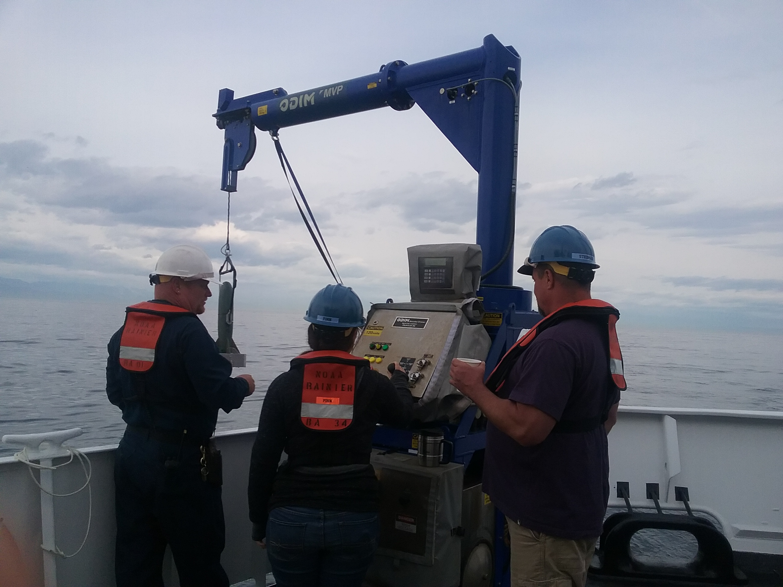 Boatswain Kinyon and Survey Technicians Finn and Stedman releasing the torpedo of the M.V.P. into the water