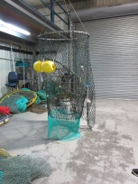 Turtle exclusion device attached to the end of nets. Turtles are stopped by the metal grid and slide out an escape chute to the right.