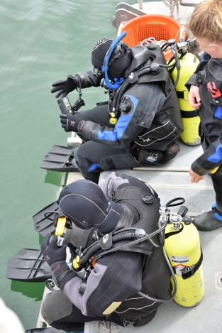Two NOAA Corps Members prepare to dive under the ship to clean sound-measuring instruments.