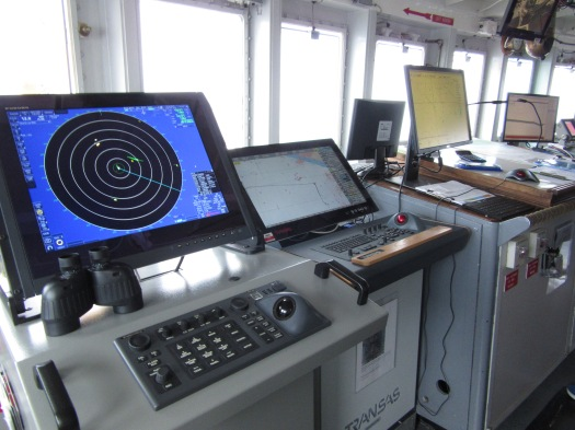 Newer instruments in Oregon II's bridge. Radar screen on left, electronic navigation charting system in the center, raster navigation charting system on right.