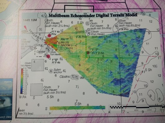 Bathymetry acquired using multibeam echosounder layered over a nautical chart.  Blue and green wave lengths penetrate further in water, so the coloring corresponds to this observation. This poster is from a previous Thomas Jefferson hydrographic survey near Savannah, Georgia. (Prepared by CHST Allison Stone)