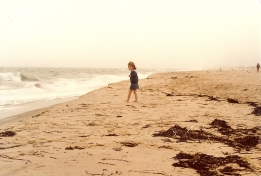 A young girl looks at the ocean.
