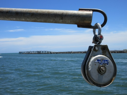 A view of water, a pier, and a pulley