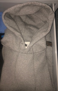 A folded grey hooded sweatshirt