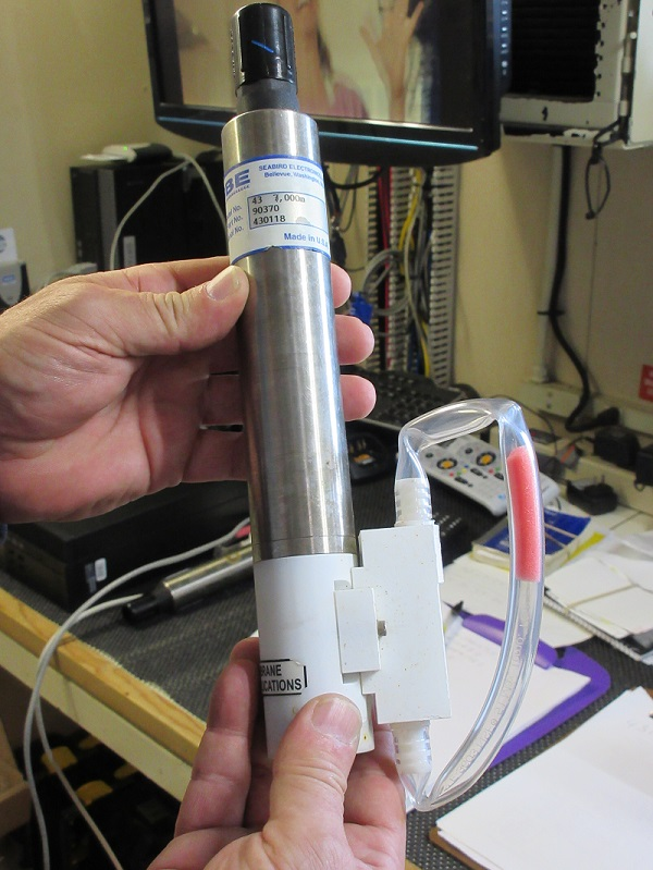 A Chief Electronics Technician holds a dissolved oxygen sensor to be mounted on the environmental profiler.