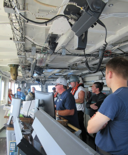 The dive team holds a post-dive debriefing on the ship's bridge.