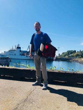 Justin Garritt standing across front of NOAA ShipBell M. Shimada