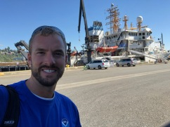 Justin Garritt standing behind NOAA ShipBell M. Shimada