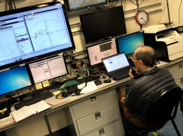 "Scientist Dezhang Chu communicates with the team at the down riggers on where to move the ""magic sphere"" for calibration"