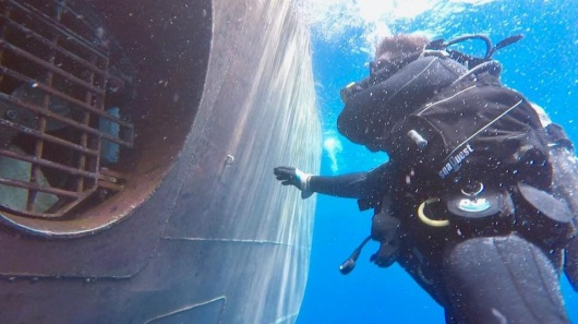 A diver inspects the bow thruster under water.