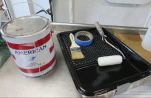 A can of white paint, a paintbrush, painting tape, a paint roller, and tray.