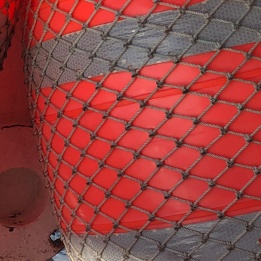 An orange longline fishing buoy covered in netting.