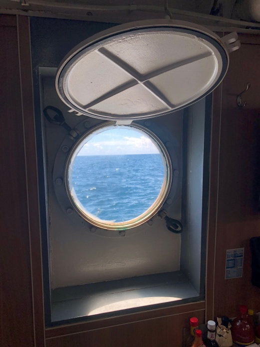 View of the water through a porthole in the galley.