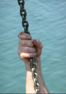 A commercial longline fisherman's hand holds on to a chain, framed against the water.