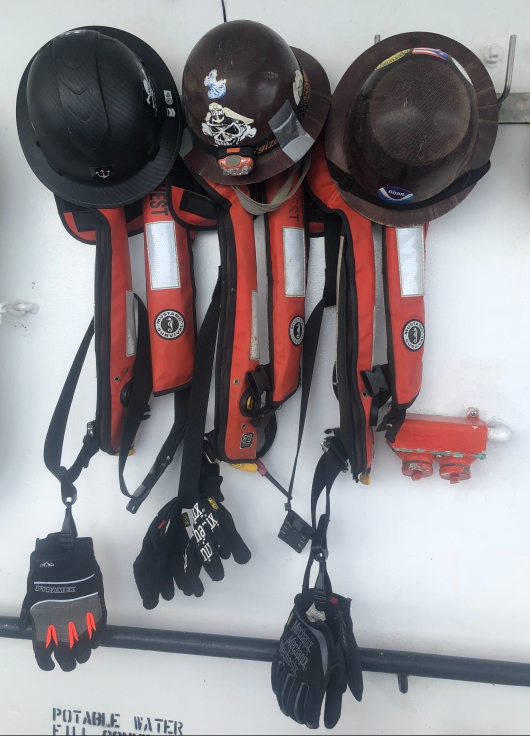 Hard hats, PFDs, and gloves belonging to the Deck Department are hanging on hooks.