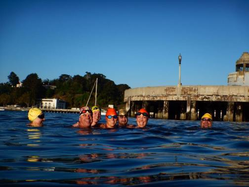 a group of swimmers wearing swimcaps and goggles treading water next to San Francisco's Muni Pier