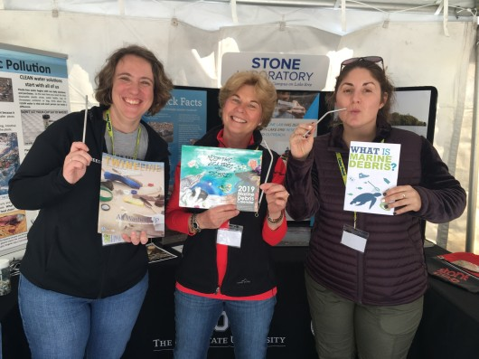 Jill and two of her colleagues are holding pamphlets about plastic pollution and encouraging people to use reusable metal straws.