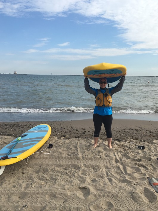 Jill is standing on the shore of Lake Erie and a sunny but cold day. She is carrying her paddleboard over her head and she and her friend are ready for a morning on the lake.