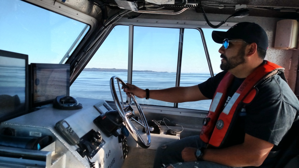 "Allan, aka ""Q"", driving the boat"